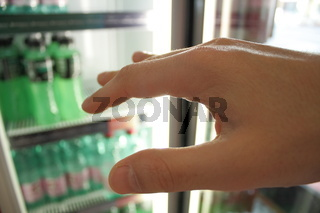 Thirsty man is grabbing with his hand for a cool drink in a fridge.