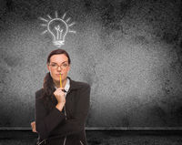 Light Bulb Drawn Above Head of Young Adult Woman With Pencil In Front of Wall with Copy Space
