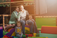 young parents and kids having fun at childrens playroom