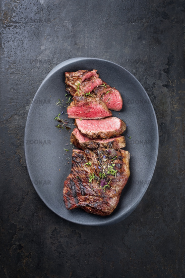 Barbecue dry aged wagyu tri tip steak sliced as top view in a modern design cast iron plate