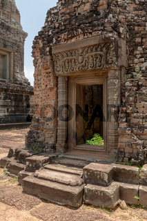 Doorway to ruined temple with decorated pediment
