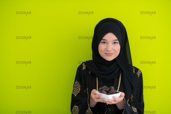 modern muslim woman holding a plate of dates in ramadan kareem on green background