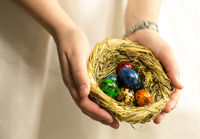 straw nest with eggs painted in different colors lie in the palm of the hand