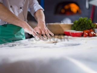 chef preparing dough for pizza