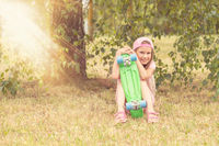 Girl with skate board sits under tree