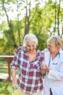 Pflegekraft hilft Seniorin beim Lauftraining