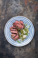 Traditional Italian barbecue aged fillet steak with vegetable slices as top view on a plate with copy space