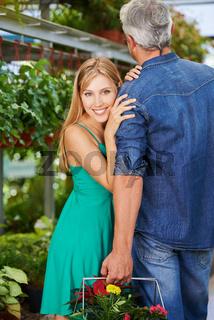 Frau lehnt an Schulter vom Mann im Gartencenter