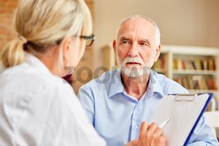 Senior Patient hört seiner Ärztin aufmerksam zu