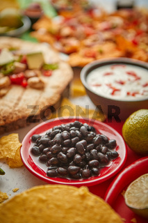Close up on black beans with various freshly made Mexican foods assortment