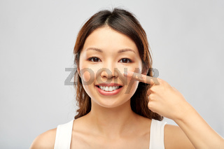 happy smiling young asian woman touching her face