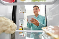 man making list of necessary food at home fridge