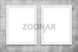 two blank picture frames hanging on concrete wall, mock-up -
