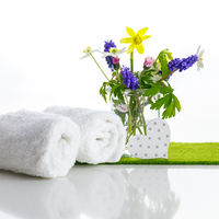 White towels with a heart next to a small bouquet of fresh flowers.