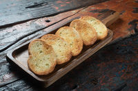 Toasted baguette slices on rustic wooden kitchen table