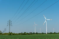 Overhead power lines and wind energy plants under a blue sky in Germany