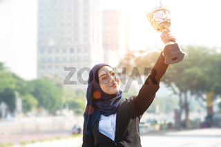 Businesswoman hand holding a trophy