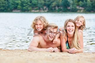 Eltern mit zwei Kindern entspannt am Strand