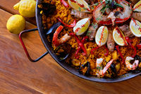 Delicious Spanish seafood paella, view from above. Cooked with sturgeon halibut fillet, peeled shrimps squids, mussels and lobster decorated with lemon slices red bell pepper in pan, close up image