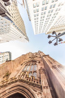 Wide angle upward view of Trinity Church at Broadway and Wall Street with surrounding skyscrapers, Lower Manhattan, New York City, USA