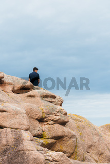 Young man on top of rock formations in Brittany