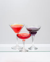 Three cocktails in glasses of various shapes.