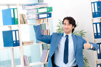 Young handsome male employee with too much work in the office