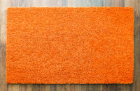 Blank Orange Welcome Mat On Wood Floor Background Ready For Your Own Text