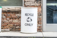 Close up of a white garbage can with a Recycle Only sign and icon