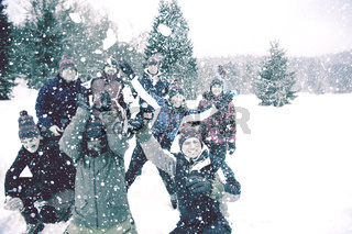 group of young people throwing snow in the air