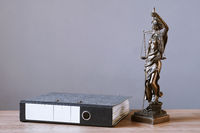 lady justice or justitia statue and file folder on desk