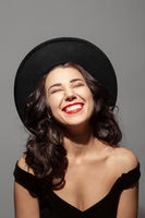 Profile portrait of a beautiful smiling lady wearing a black hat