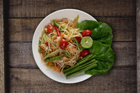 Top view Thai food rice noodle papaya salad on wooden table