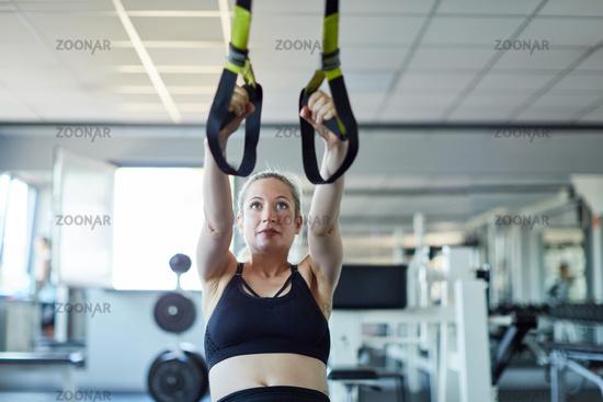 Junge Frau beim Suspension oder Sling Training