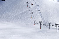 Snowy ski slope and chair-lift at winter morning