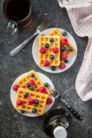 Waffles, maple sirup, blueberries and raspberries.
