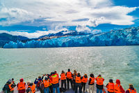 Tourists with orange color life jackets on a sightseeing boat excursion to the Grey Glacier