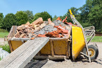 Container with debris and wheelbarrow outside