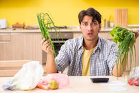 Young man calculating expences for vegetables in kitchen