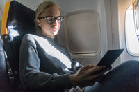 Woman wearing glasses reading on digital e-reader while traveling by airplane.