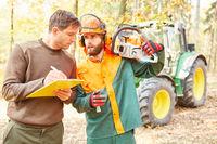 Forstwirt mit Checkliste und Holzfäller mit Motorsäge