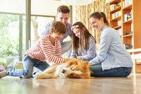 Eltern und Kinder streicheln gemeinsam Hund