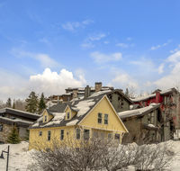 Houses on snow covered ground against blue sky with puffy clouds in winter