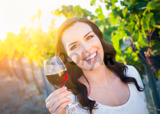 Beautiful Young Adult Woman Enjoying Glass of Wine Tasting In The Vineyard