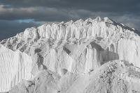 hill of pure sea salt under dark clouds