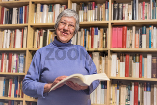 Senior woman reading a book at home. Happy expression. A blurred library is in the background.