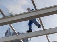 Worker cleaning large glass roof over swimming pool