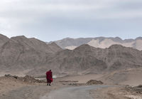 Monk walking with mountain backdrop, Ladakh, India