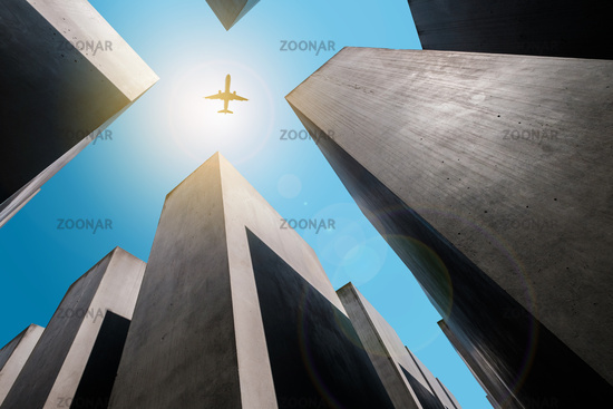 Airplane flying over Memorial to the murdered jews / the Holocaust memorial in  Berlin