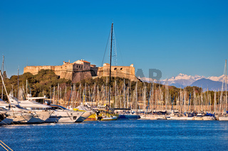Antibes harbor and old fortress with Alps snow peaks background view